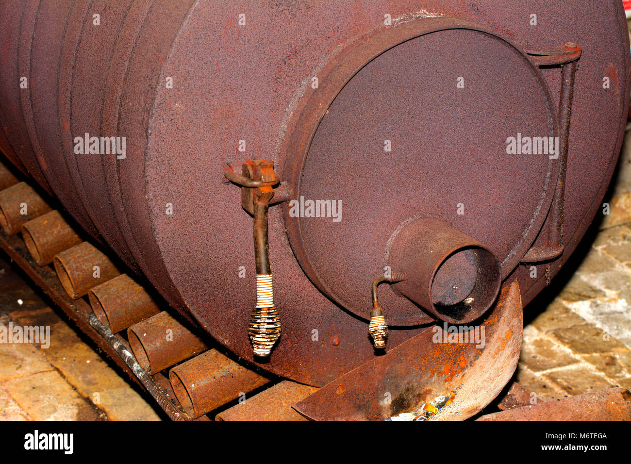 An old rusty stove for heating premises in winter in an abandoned and destroyed factory amidst chaos. Destruction - Stock Image