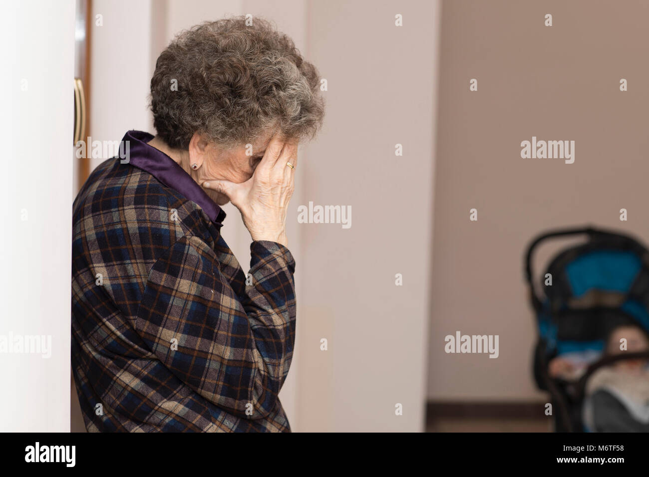 Old woman shows her worries about baby in the trolley - Stock Image
