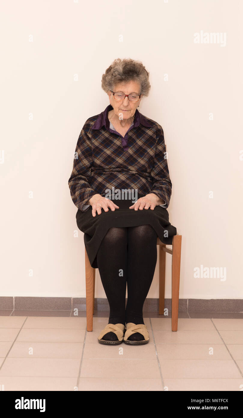 f95aae399c3c2 Old Italian woman is sitting at the chair in the corridor. Free space for a