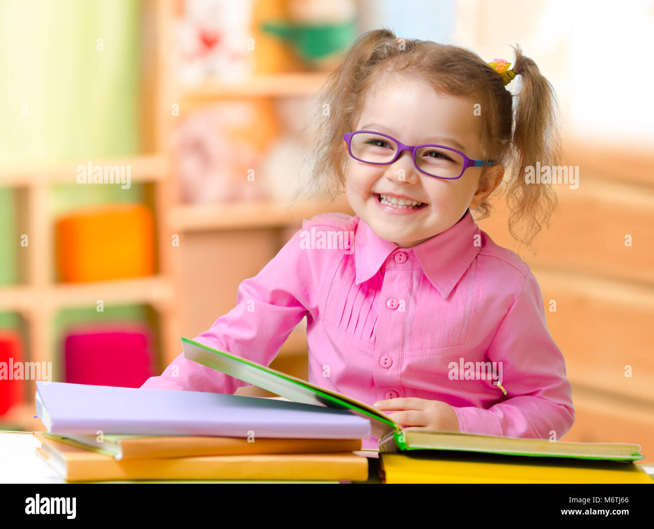 Kid in eyeglasses or spectacles reading books in her room - Stock Image