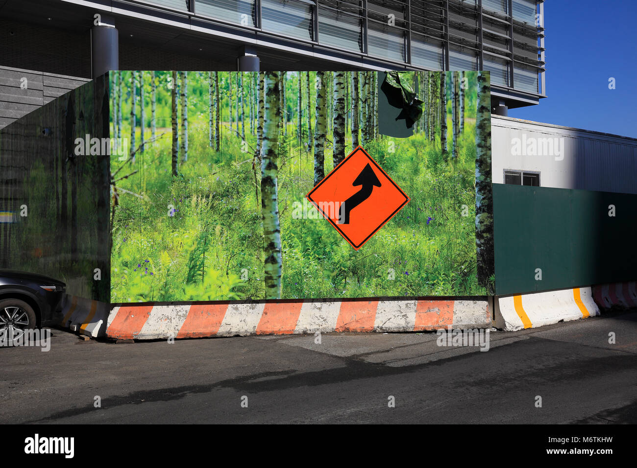 Deviation warning traffic sign on fenced-in construction site - Stock Image