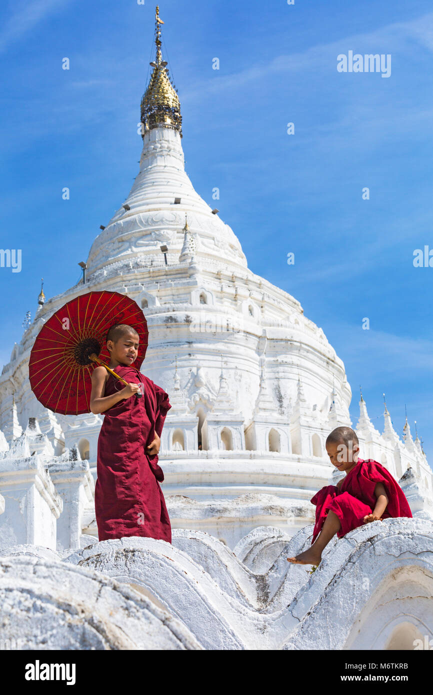 Young novice Buddhist monks, one holding parasol & one sitting at Myatheindan Pagoda (also known as Hsinbyume - Stock Image