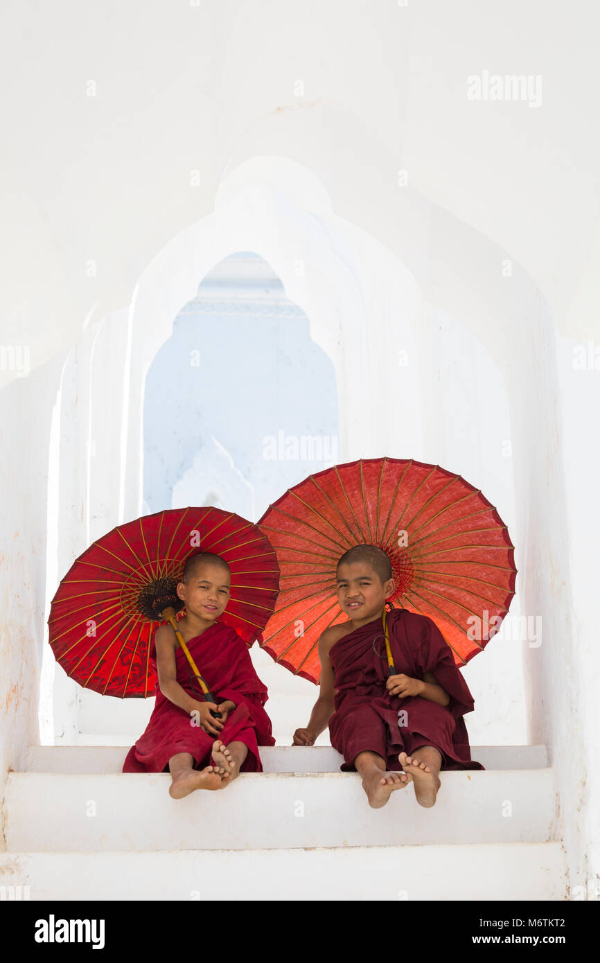 Young novice Buddhist monks holding parasols at Myatheindan Pagoda (also known as Hsinbyume Pagoda), Mingun, Myanmar Stock Photo