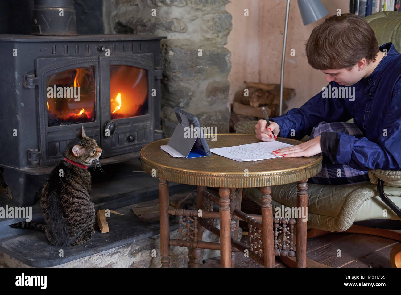 A teenage girl studying by a fire. - Stock Image
