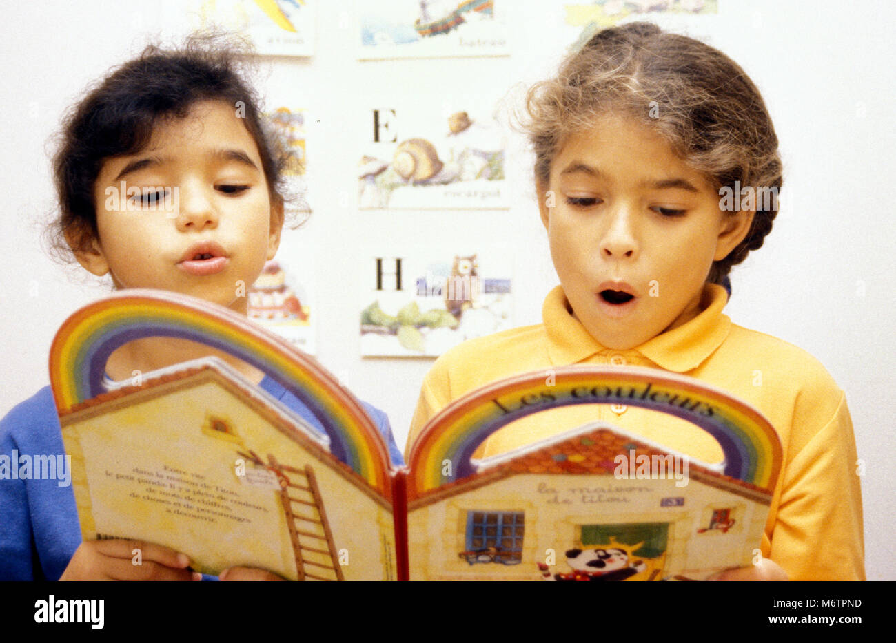 Two little girls reading out loud from french book on colours - Stock Image