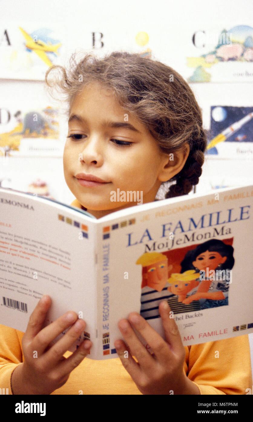 little girl reading french book La Familia, the Family - Stock Image