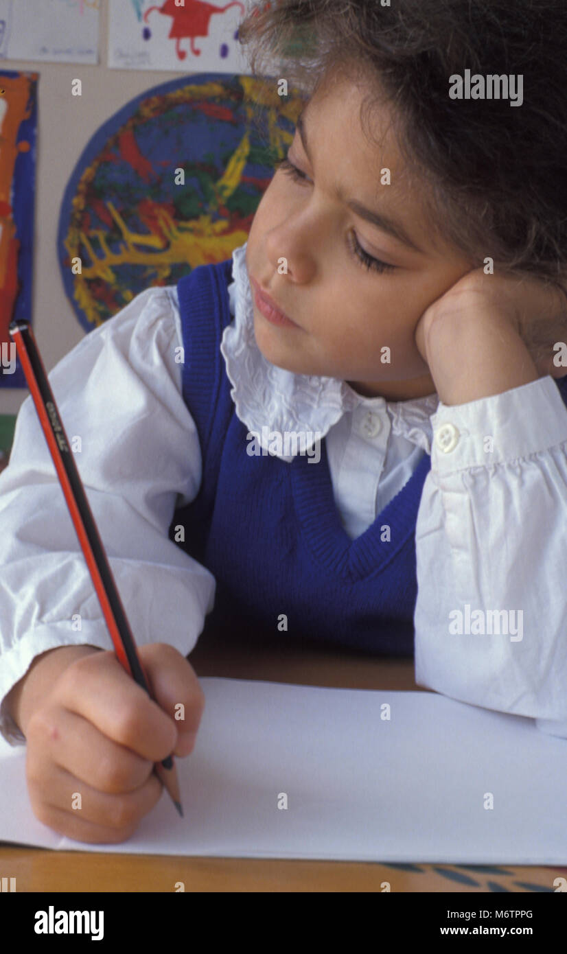 little girl sitting at desk pondering over pencil and paper - Stock Image