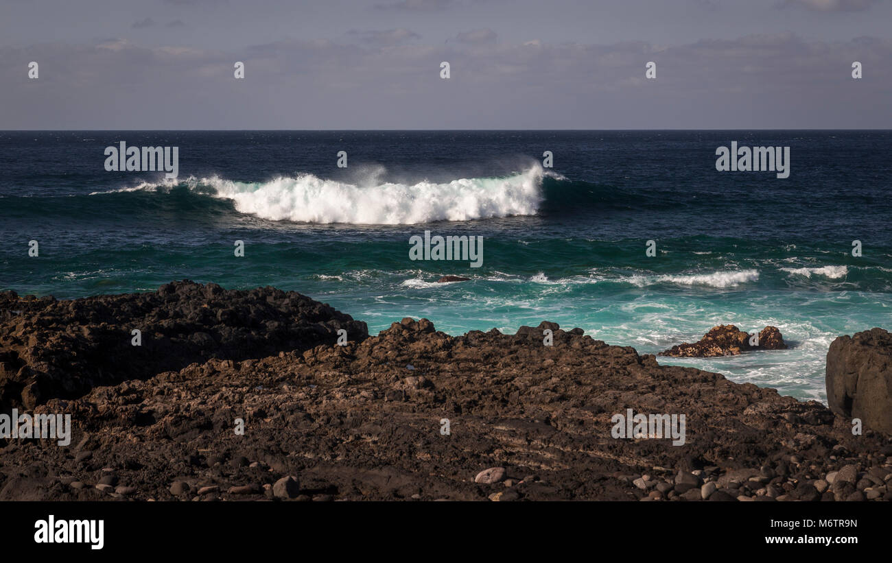 Atlantic wave breaking on the volcanic shore of Gran Canaria in the Canary Islands - Stock Image