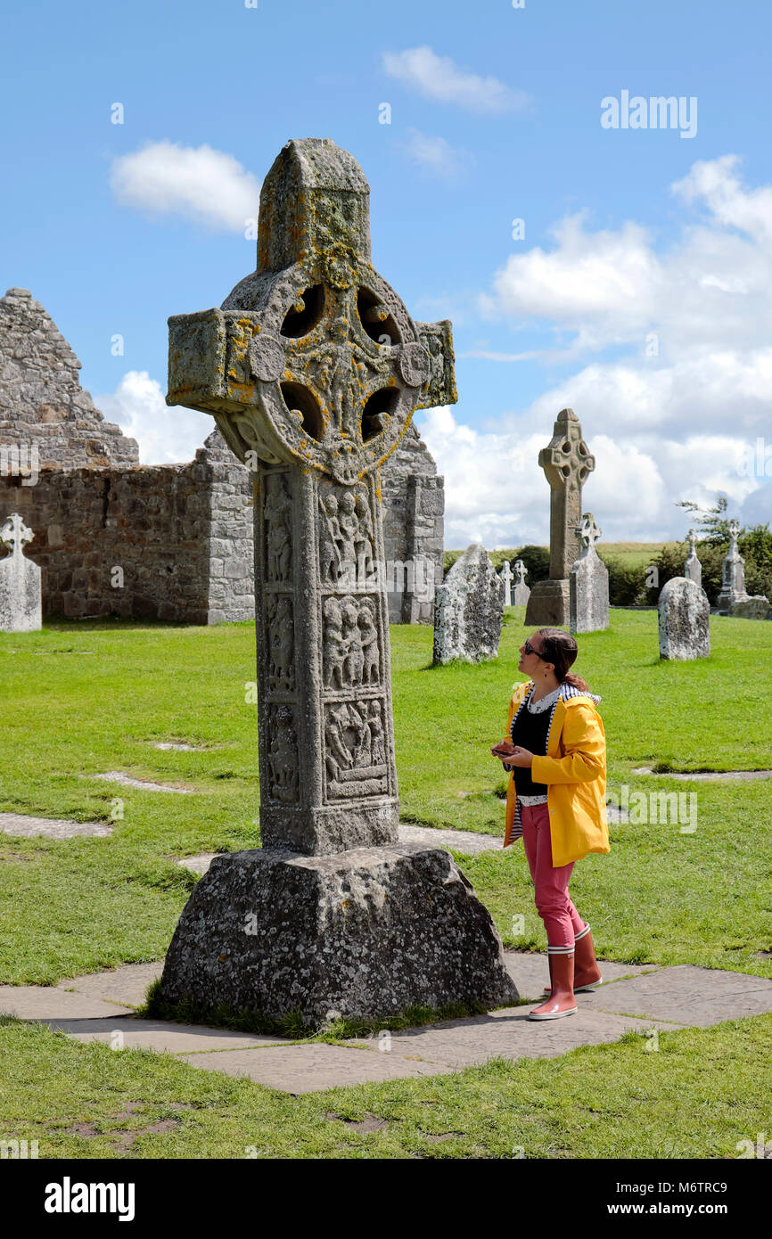 Woman standing next to the Cross of the Scriptures, Clonmacnoise Monastery, County Offaly, Ireland - Stock Image