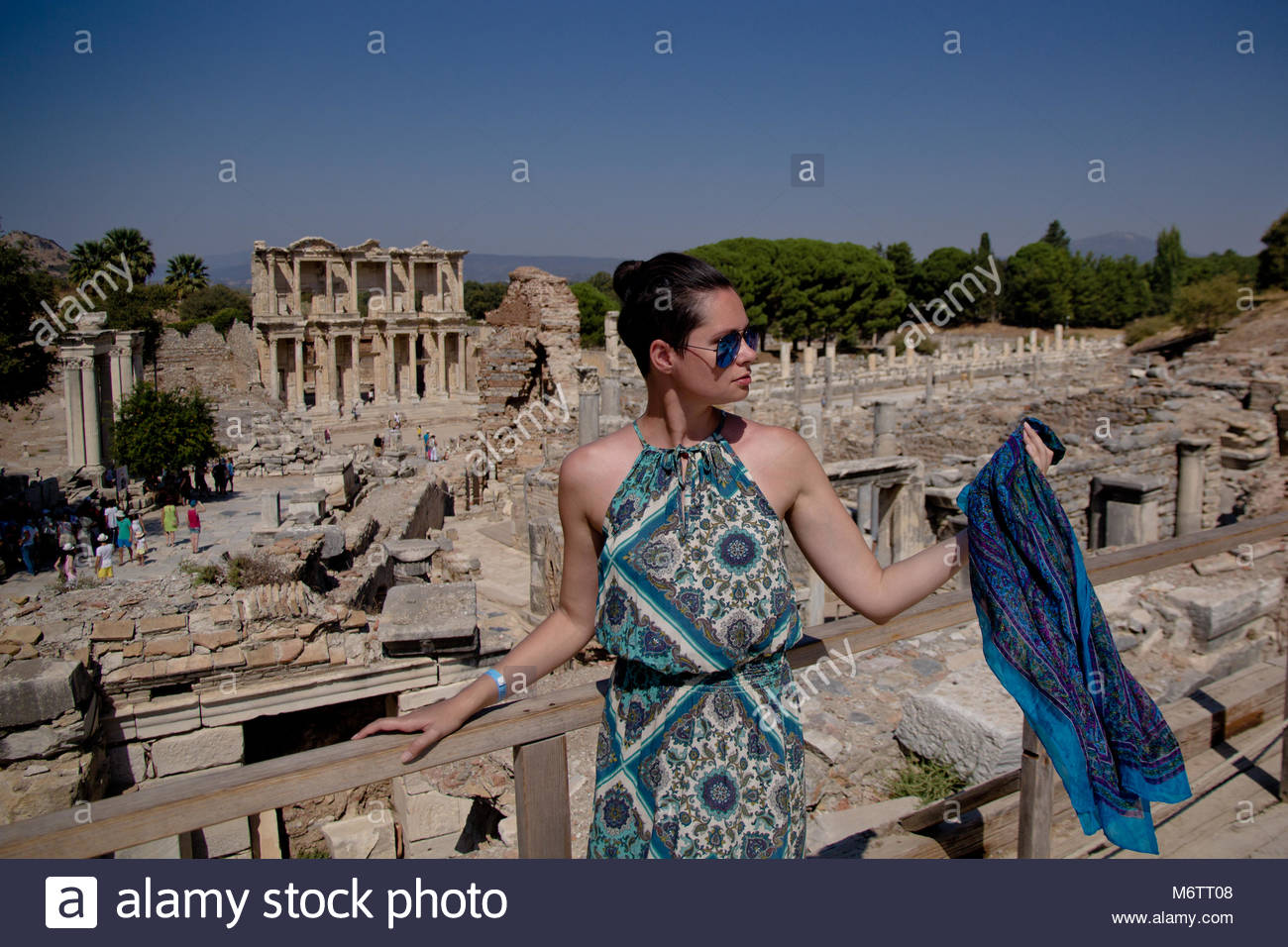 Gorgeous young woman wearing in stylish silk sundress with geometric pattern on it and big round sunglasses  is - Stock Image