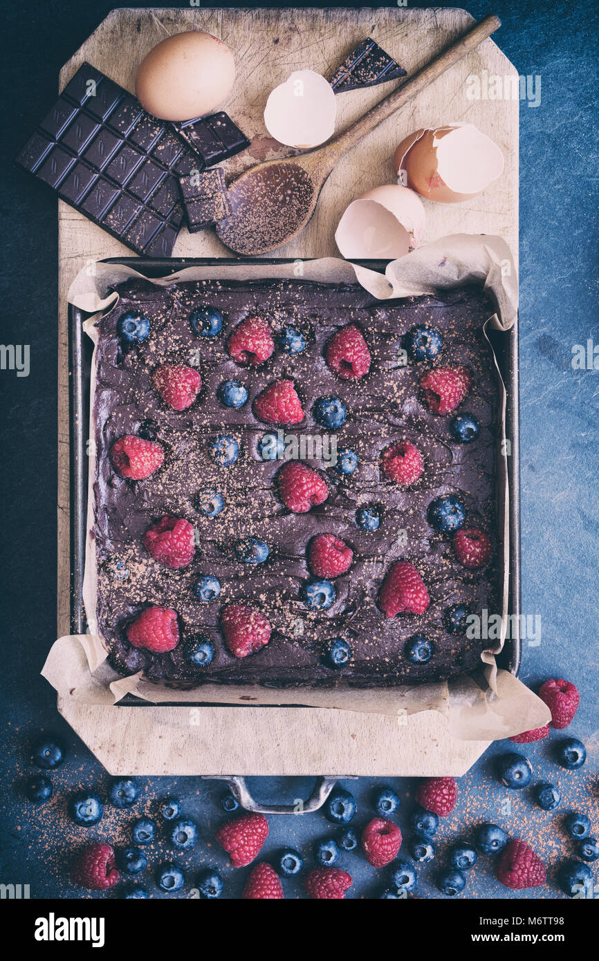 Homemade raw chocolate raspberry and blueberry brownie mixture in a baking tray with ingredients on a slate background - Stock Image