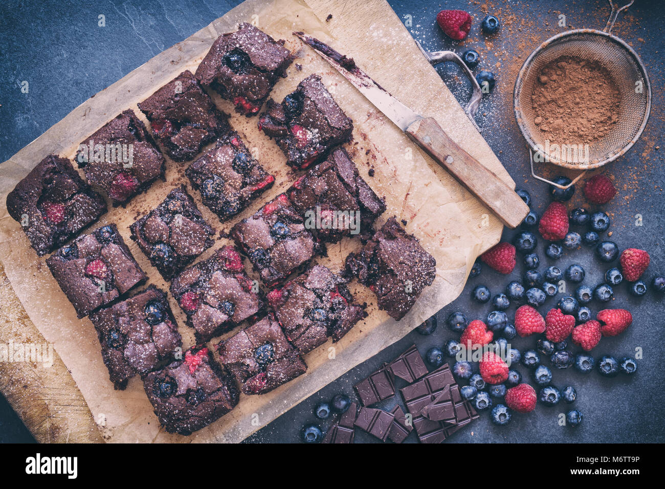 Homemade Chocolate raspberry and blueberry brownies with ingredients on a slate background. - Stock Image