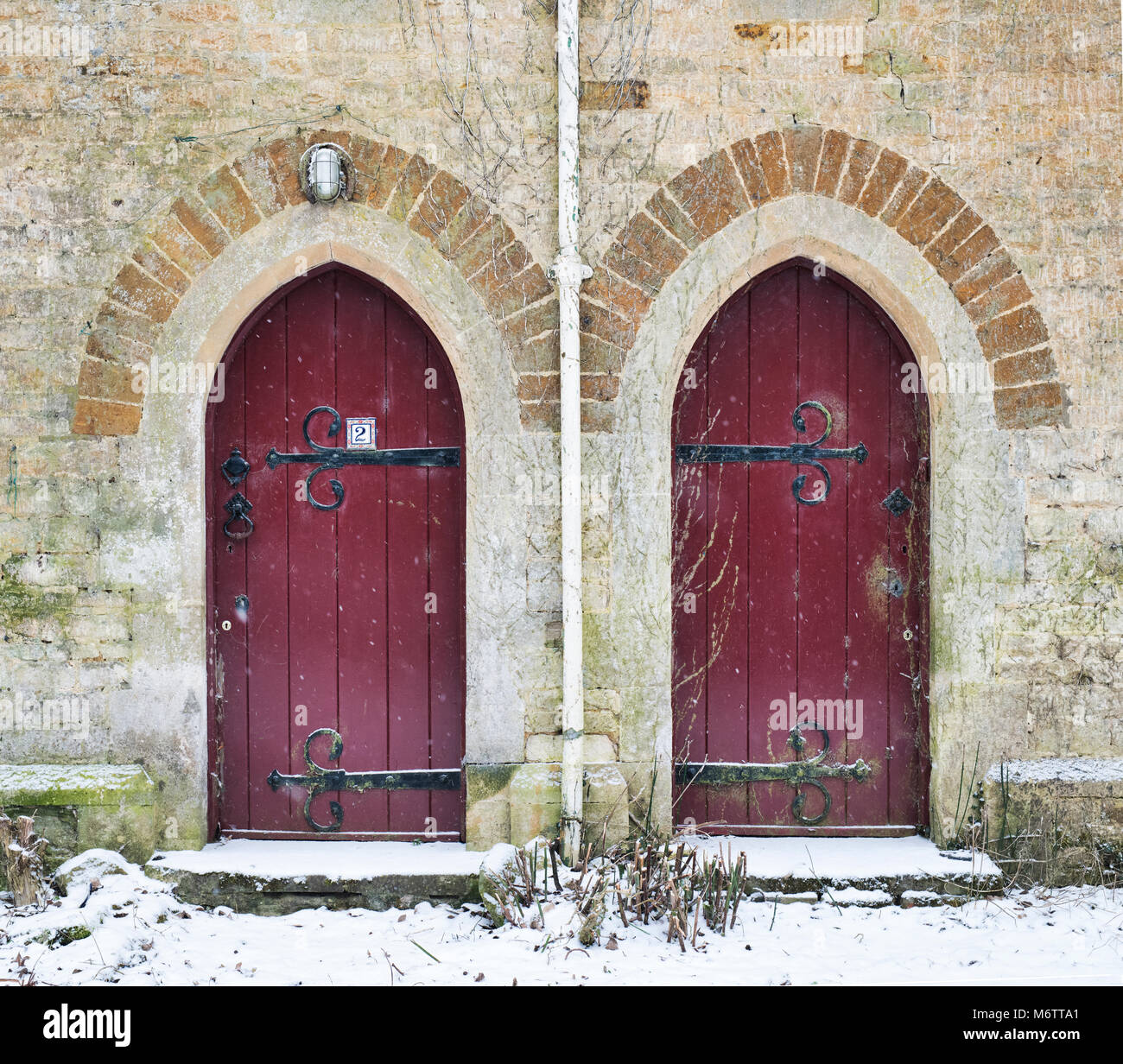 Two dark red / maroon arched cottage doors in Little Tew in the winter snow. Little Tew, Cotswolds, Oxfordshire, - Stock Image