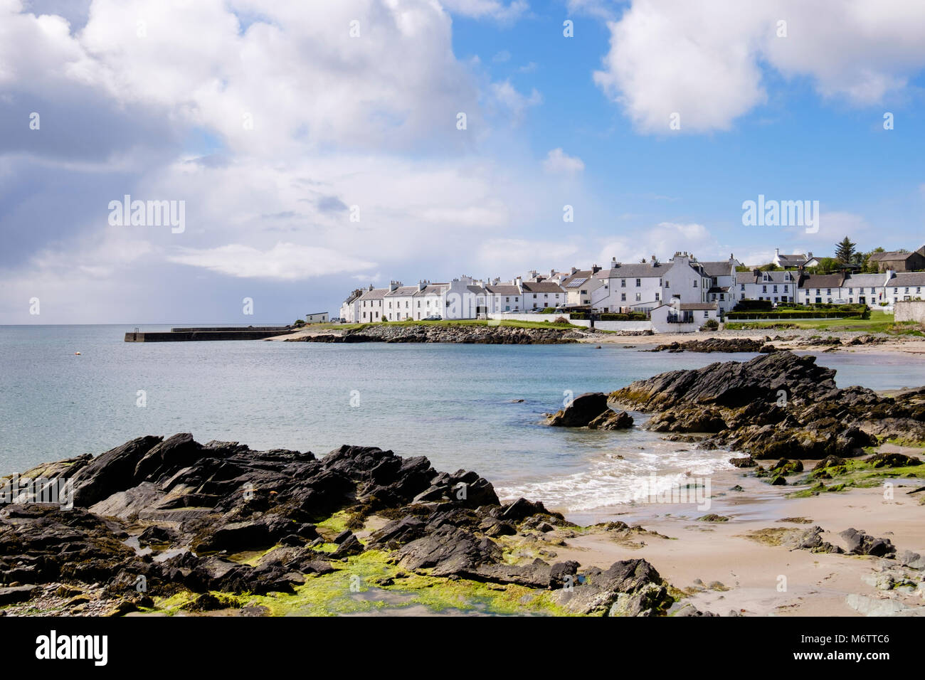 View along rocky Scottish island coast of Loch Indaal to Port Charlotte, Isle of Islay, Argyll and Bute, Inner Hebrides, - Stock Image