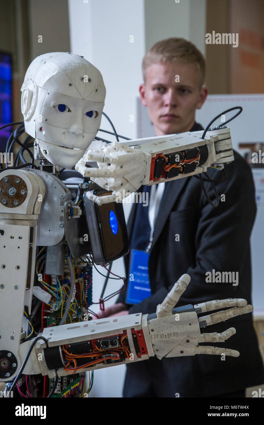A young scientist testing an anthropoid robot at the Robostation, at Moscow's VDNKh Exhibition Center in Russia - Stock Image