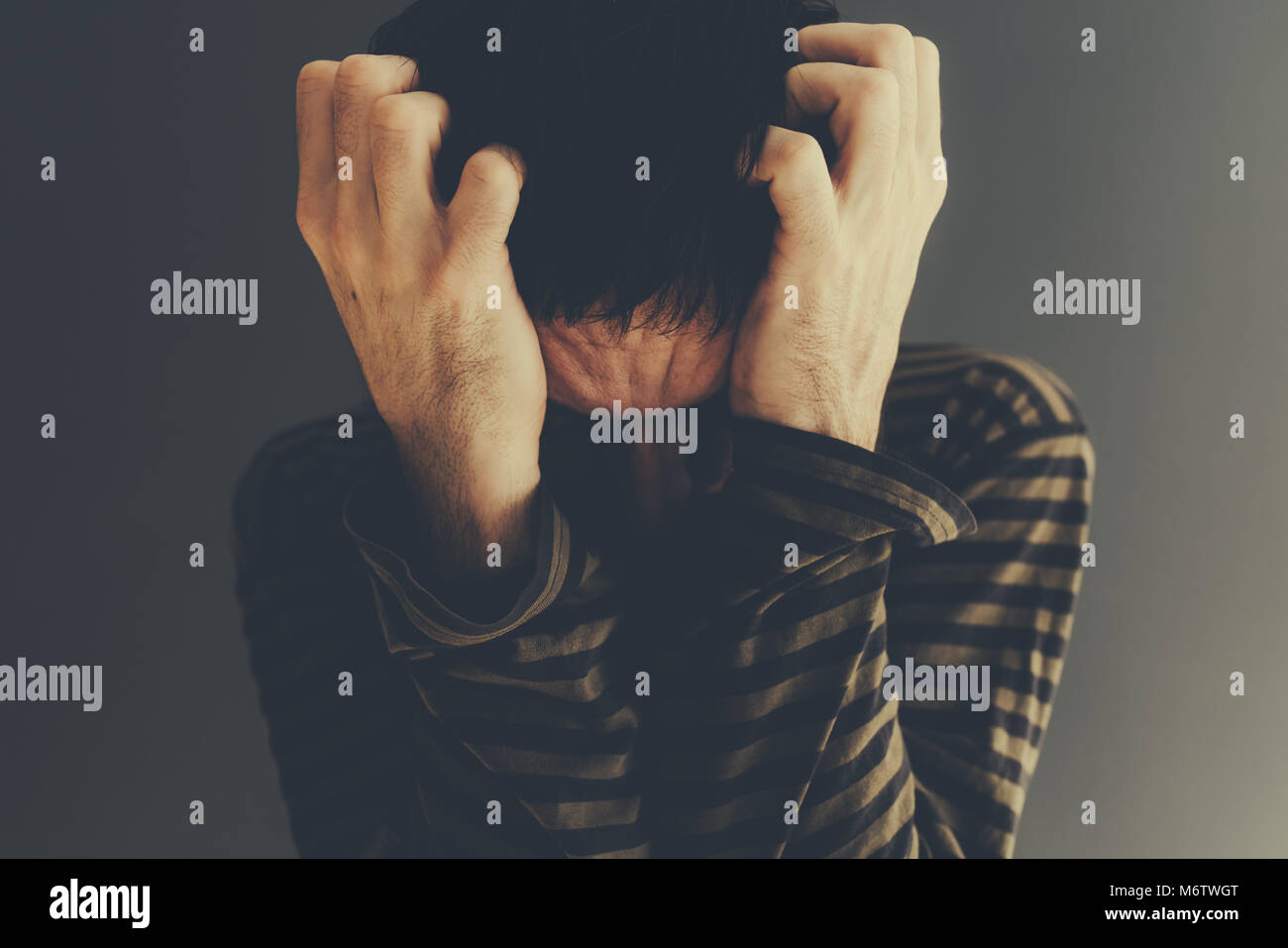 Desperate man crying alone, low key portrait with selective focus - Stock Image