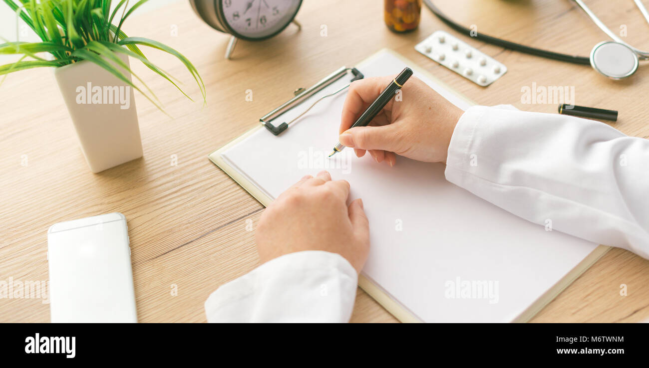 Female doctor writing notes, patient's medical history or medicine prescription on clipboard paper during medical - Stock Image