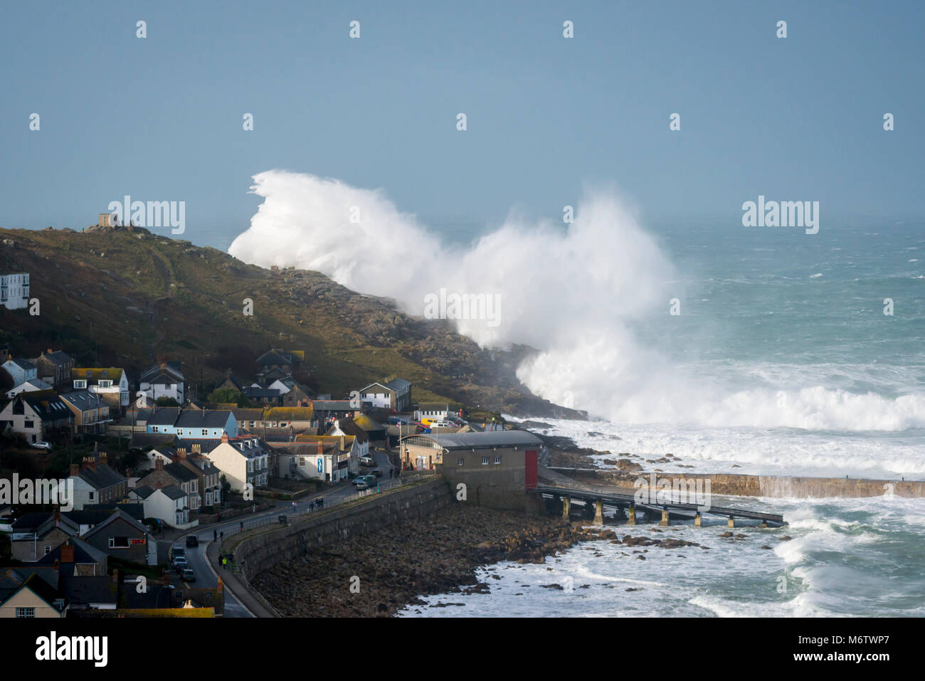 A massive wave at Sennen Cove threatens to engulf the village - Stock Image
