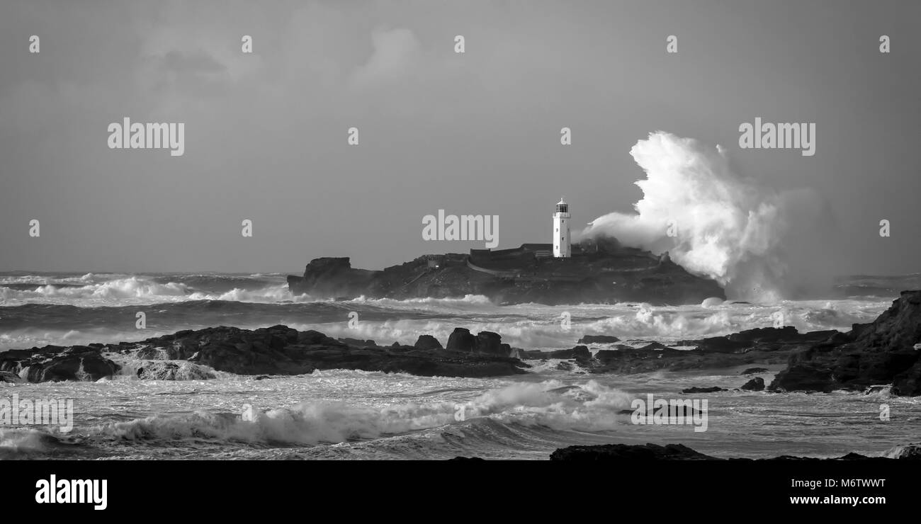 A massive wave breaks over Godrevy lighthouse, Cornwall UK - Stock Image