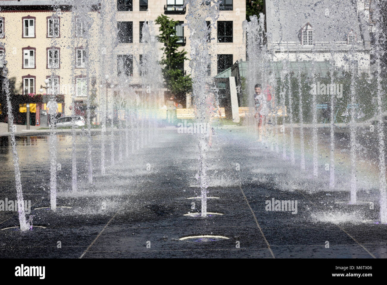 Fountains in Quebec City with a rainbow effect and children playing in the background on a sunny day. - Stock Image