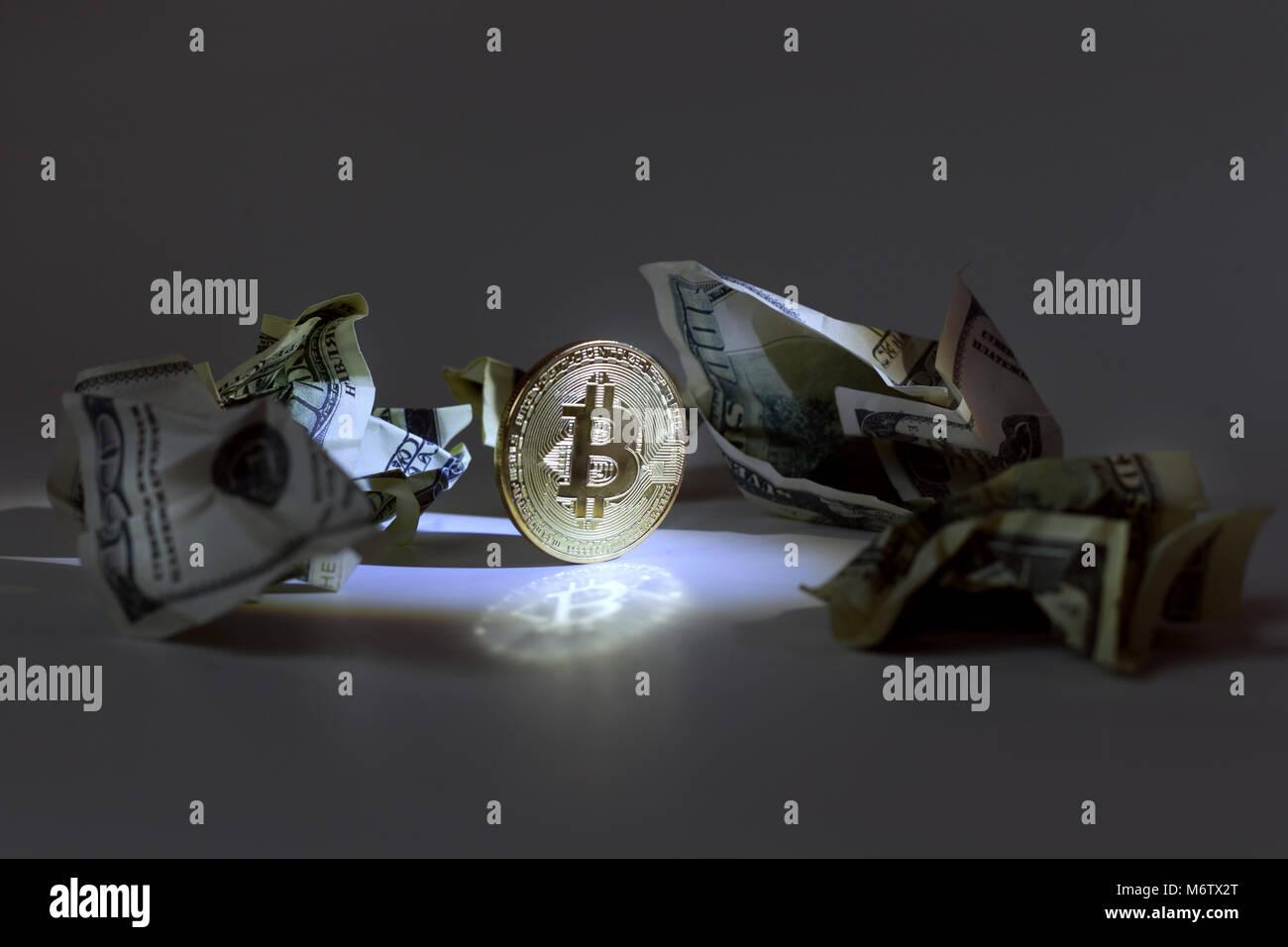 Gold coin bitcoin among crumpled dollar bills. - Stock Image