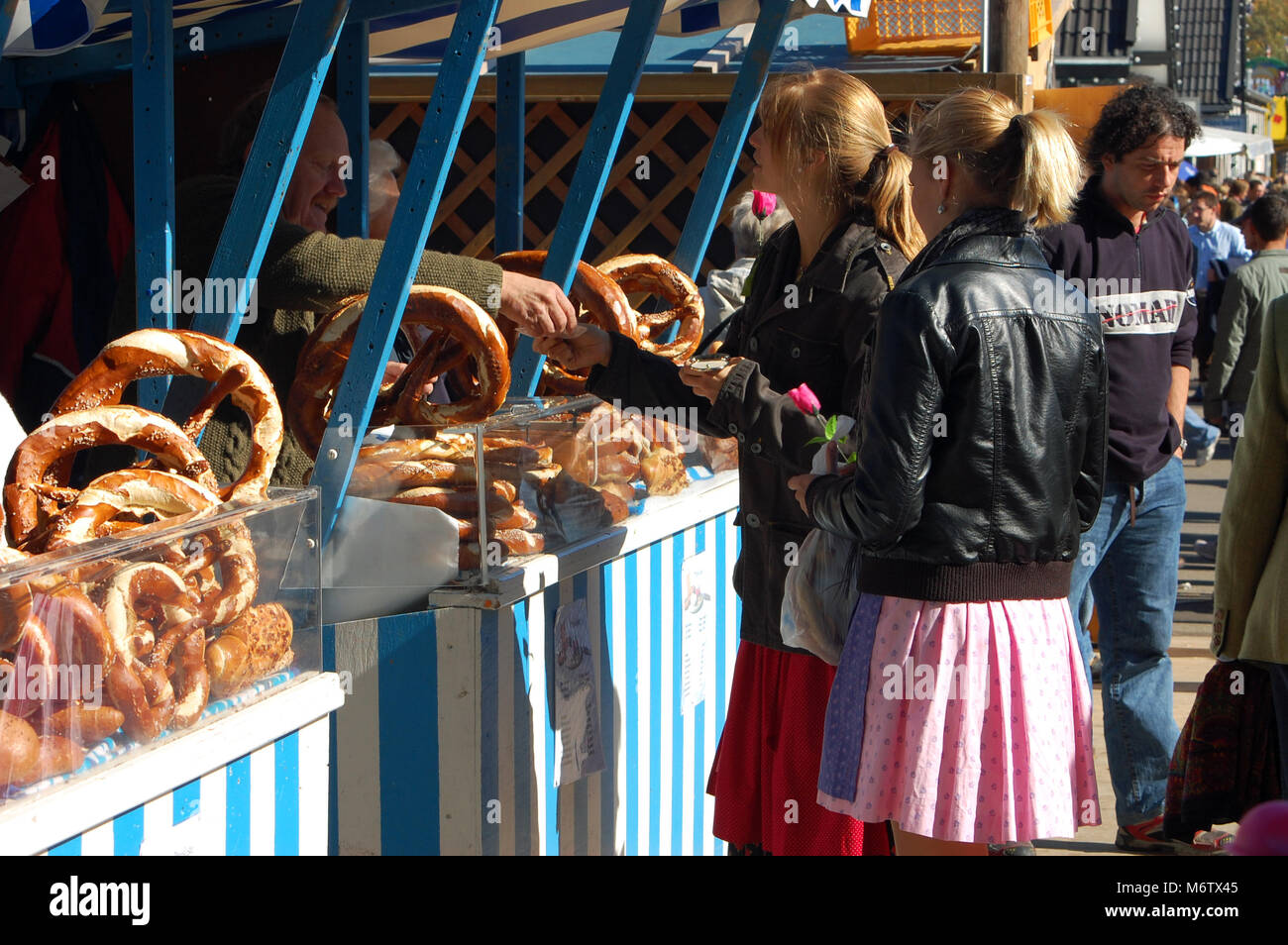 Two people buying brezen or pretzels at a stall at the Oktoberfest in the city of Munich in Germany - Stock Image