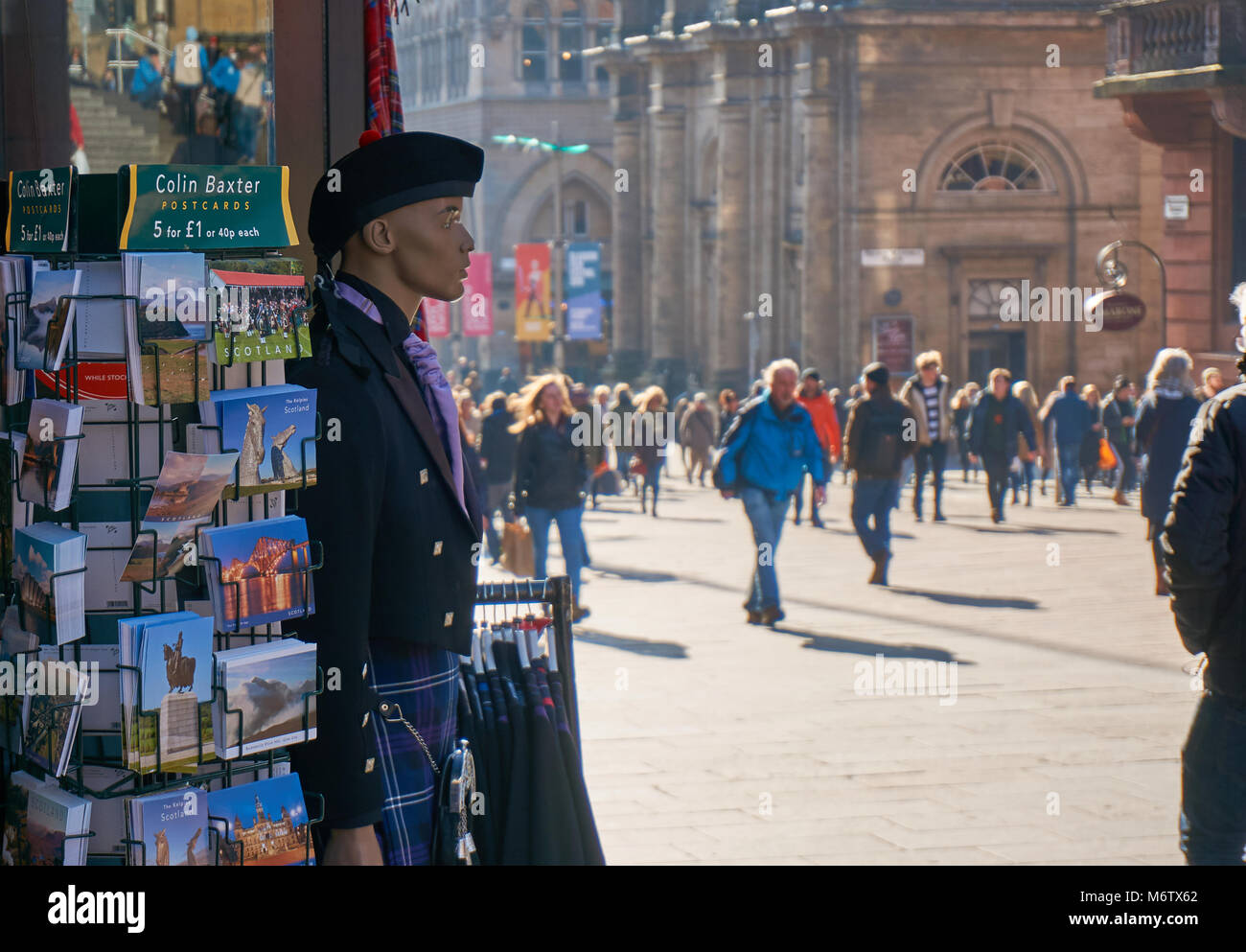 A  rack with postcards and a mannequin dressed in traditional Scottish kilt outside a souvenirs shop in Glasgow, - Stock Image