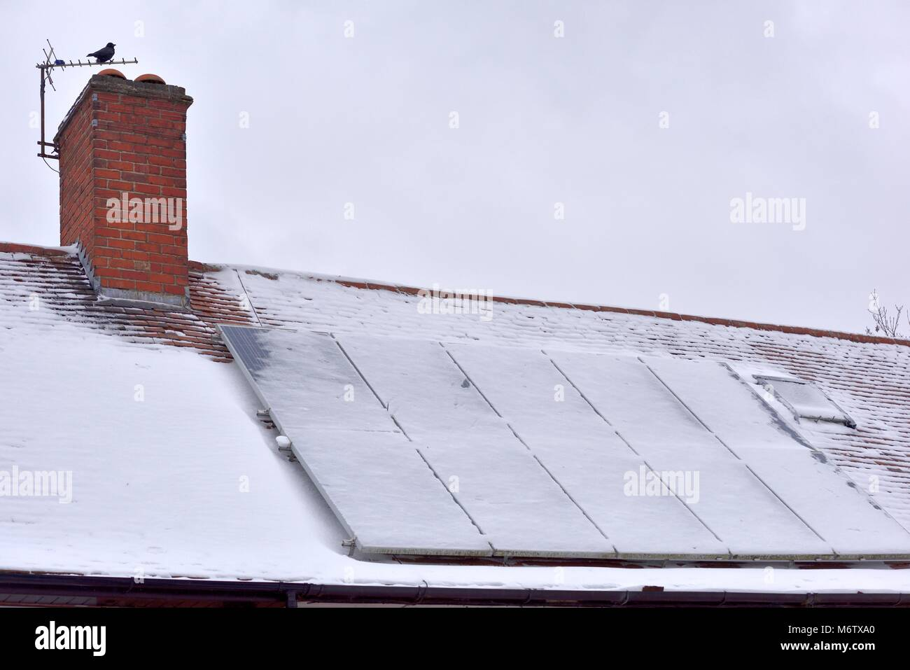 Solar energy panels on a roof covered in snow - Stock Image