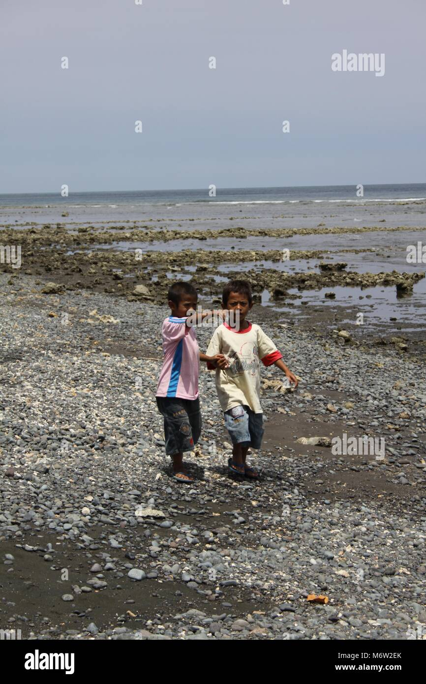 Beautiful quiet beaches in the northwest of Bali Children walking ashore - Stock Image