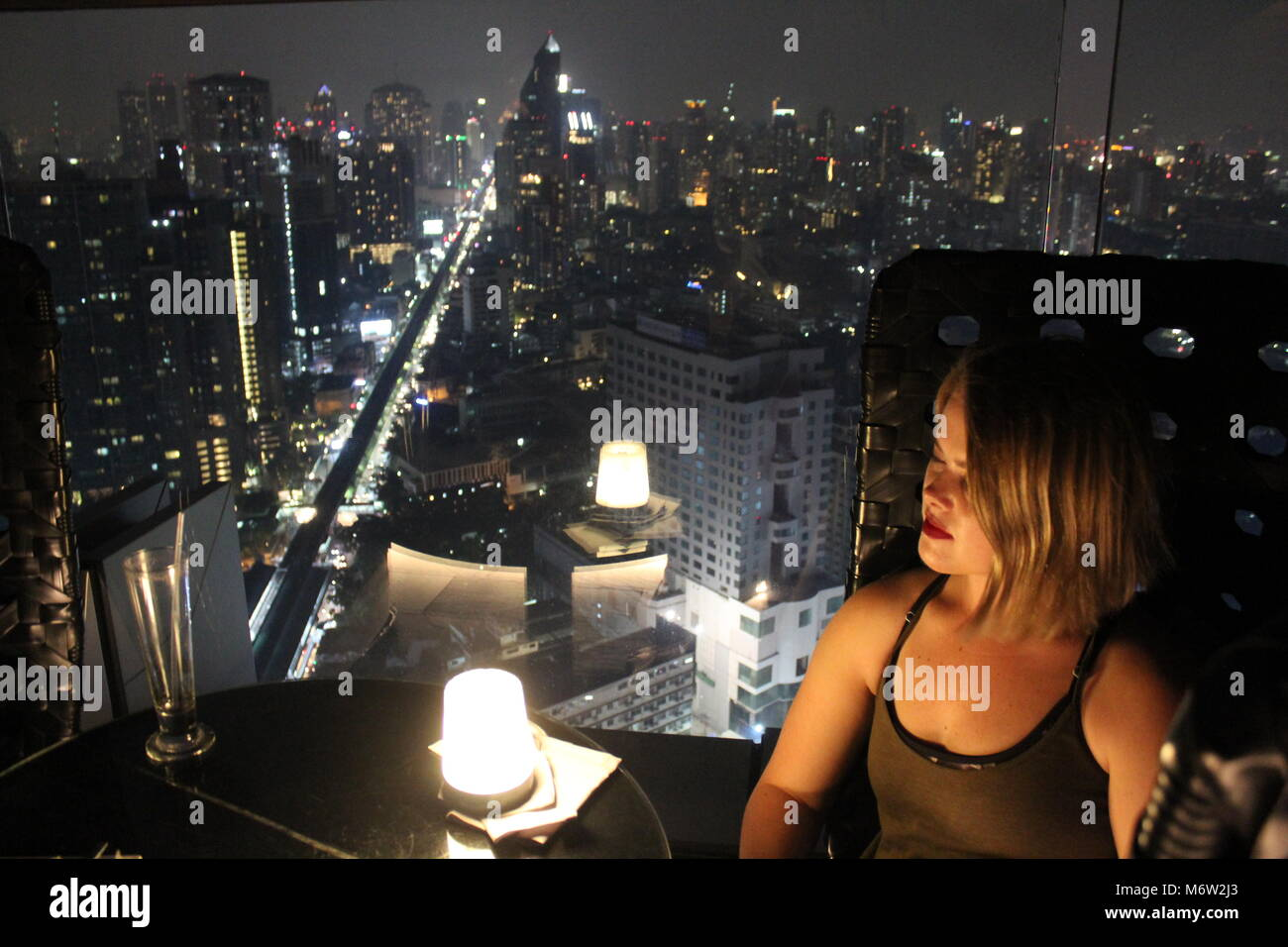 A view of the Bangkok city skyline with a woman enjoying it. - Stock Image