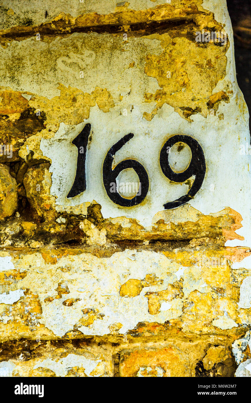 House number 169 in cast iron numbering on a yellow stone wall. - Stock Image