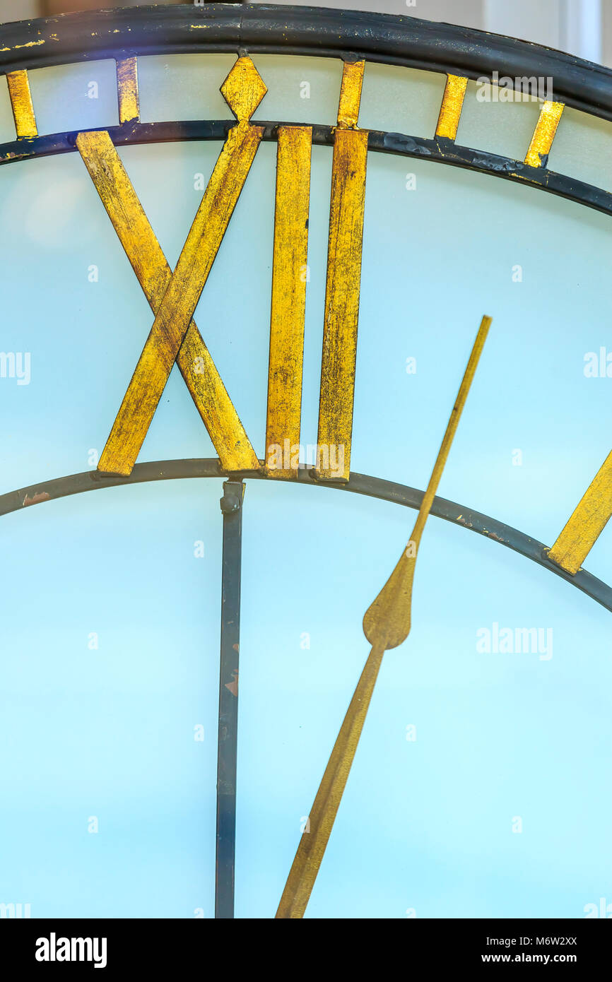 A white clock with gold fingers showing the time at just after twelve o'clock, midnight or midday. - Stock Image