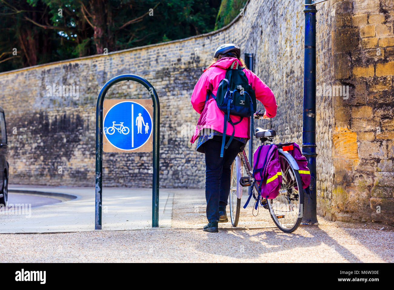A cyclist having to dismount and walk through a passage. - Stock Image