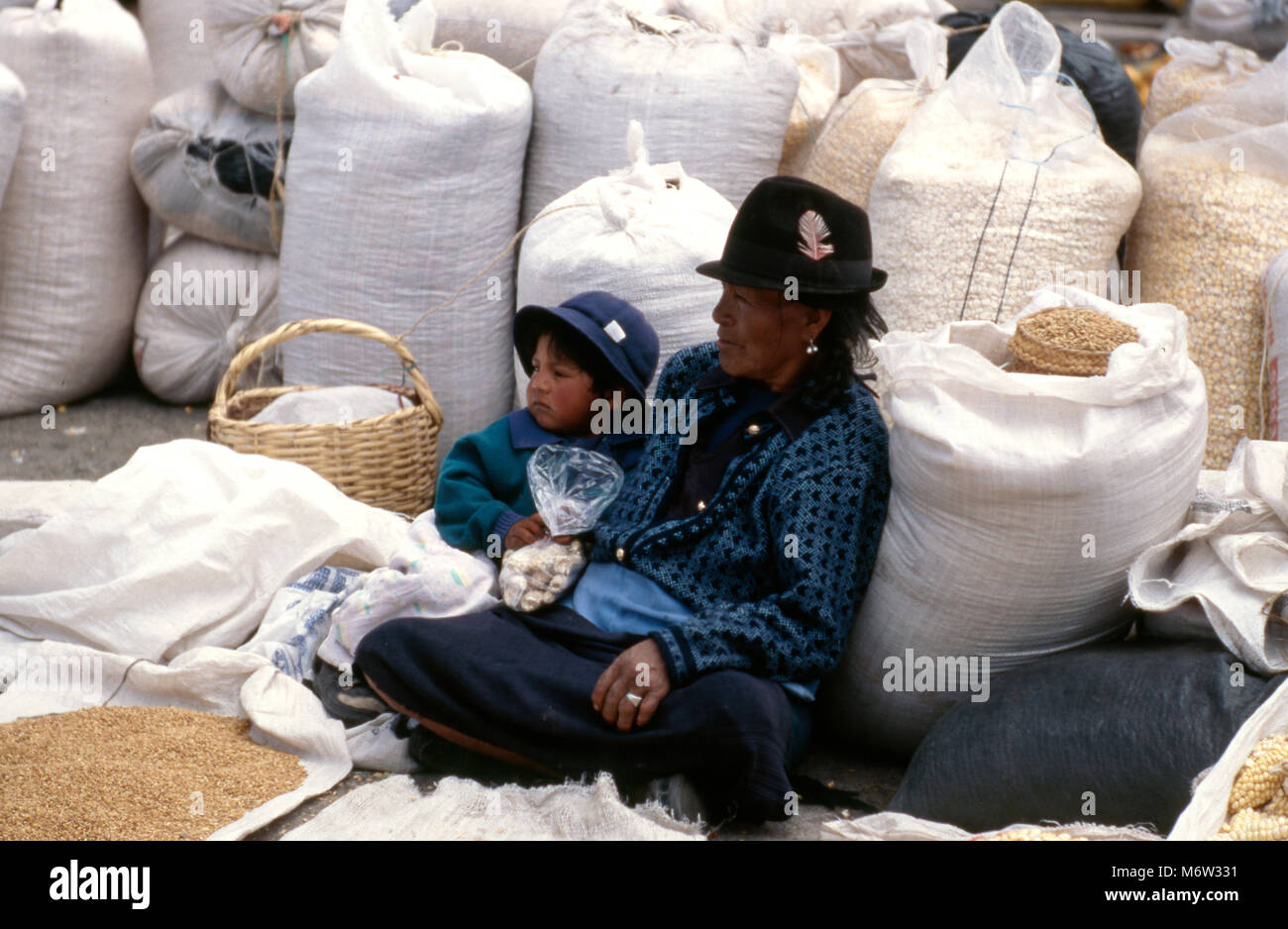 An indigenous, ethnic Quichua (Quechua) woman with her son selling grain at the market in Latacunda, Ecuador. - Stock Image