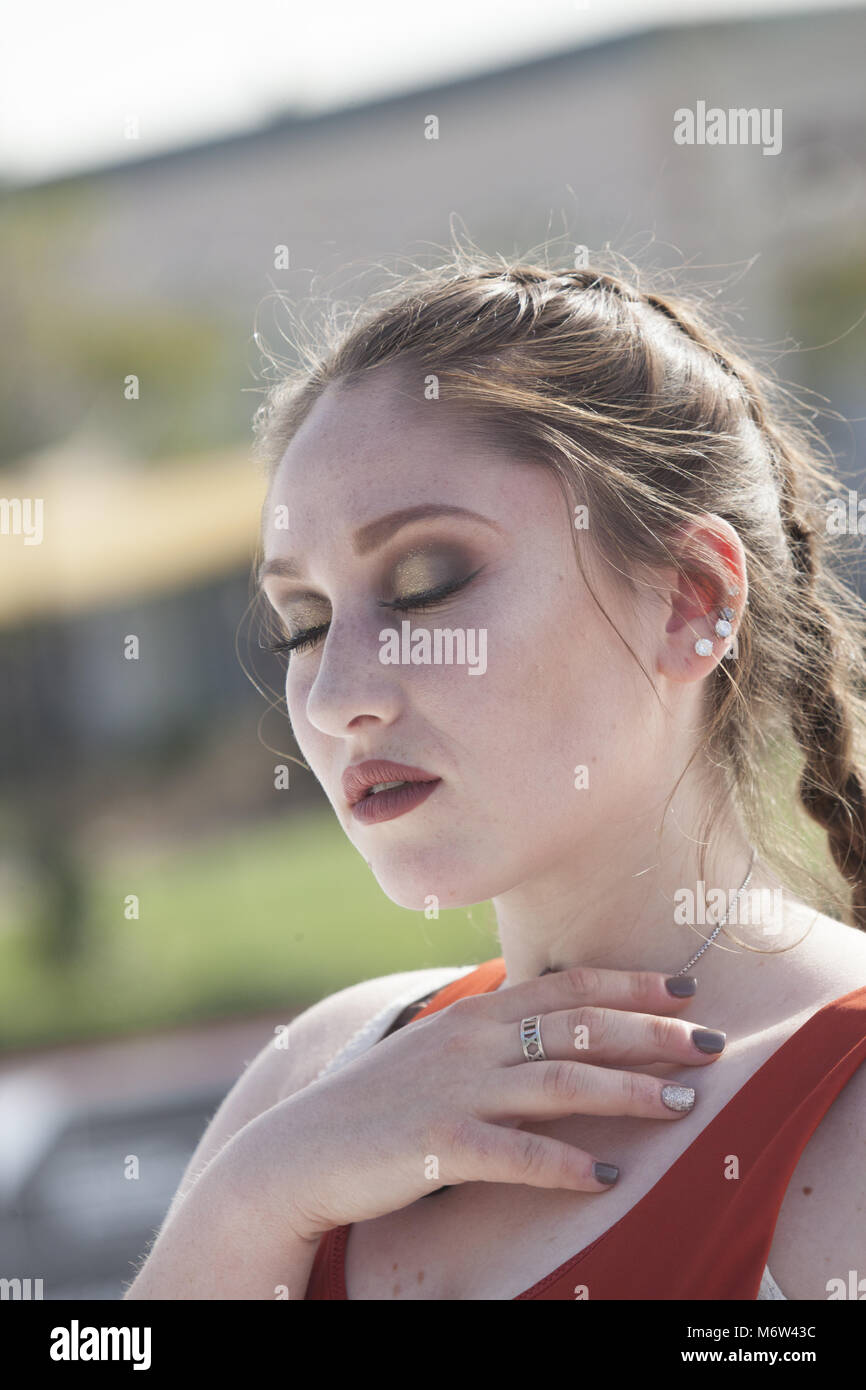 Outdoor close up portrait of a young woman with dramatic eye makeup and a braid - Stock Image