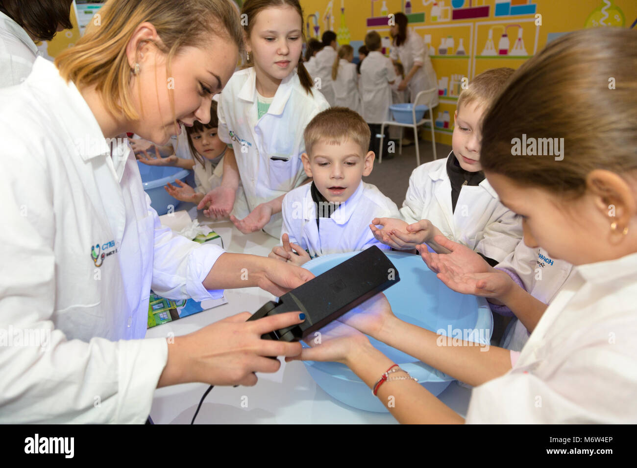 Doctor checks microbes in children's hands at the children's interactive exhibition 'Become a doctor - Stock Image
