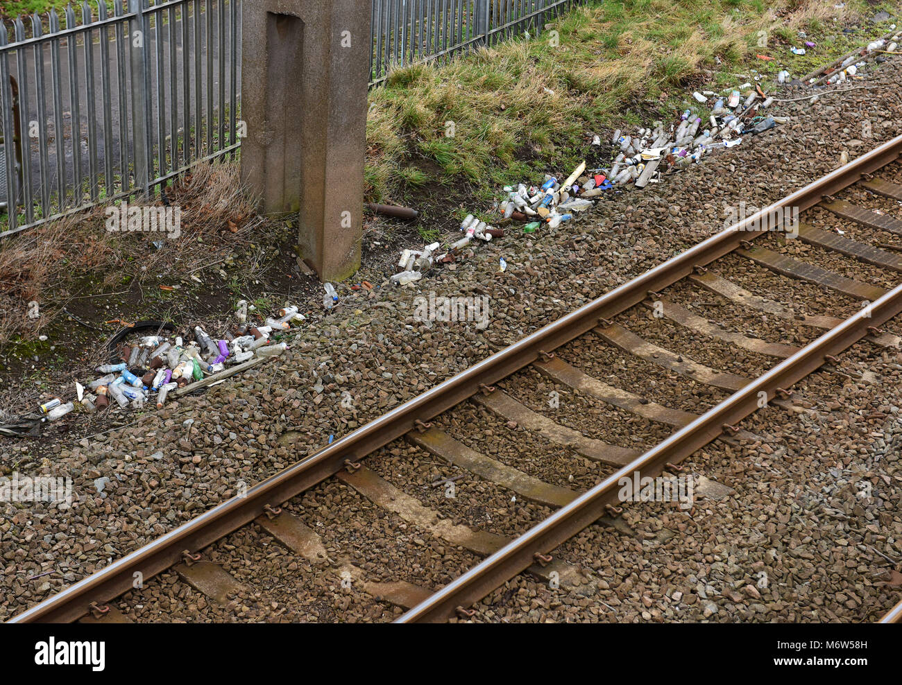 Railway track littered with plastic bottles and drinks cans thrown from trains by passengers England, Britain, Uk - Stock Image