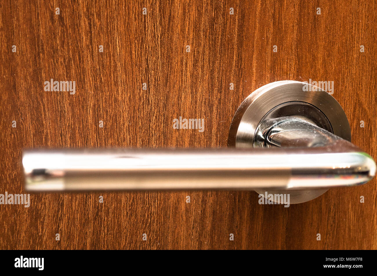Handle and wooden door close up. Nice and elegant wooden door with silver handle. - Stock Image