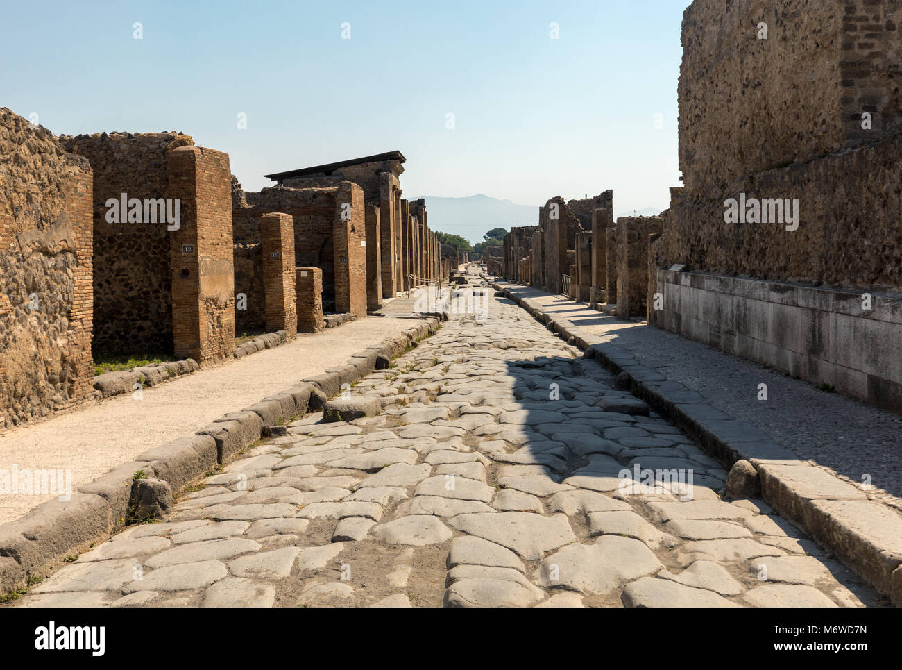 An ancient cobbled street in the ruins of Pompeii, Italy. - Stock Image