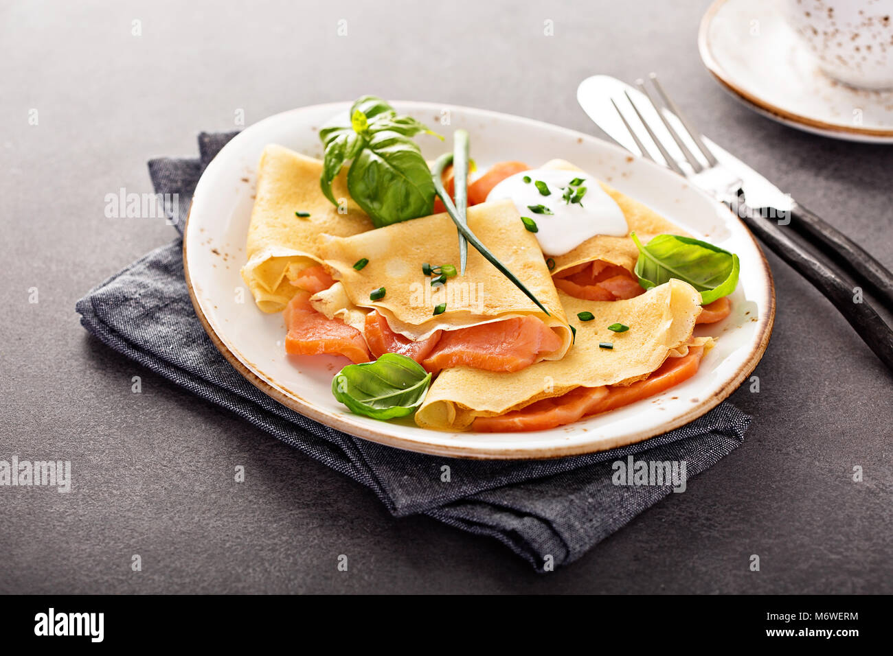 Savory crepes with salmon filling and sour cream - Stock Image