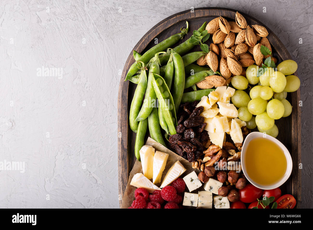Cheese and vegetables board with nuts and honey - Stock Image