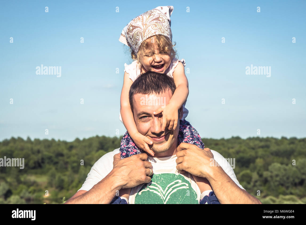 Father cute daughter having fun together as family lifestyle portrait in front of  blue sky. Happy father holding - Stock Image