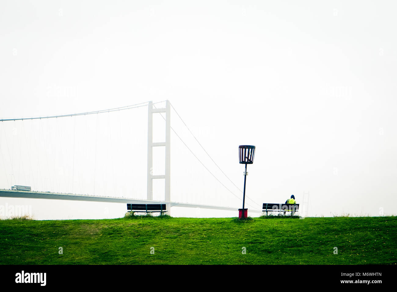 Lone person in hi vis jacket sits by the south bank of Humber bridge on  misty morning, North Lincolnshire, England, - Stock Image