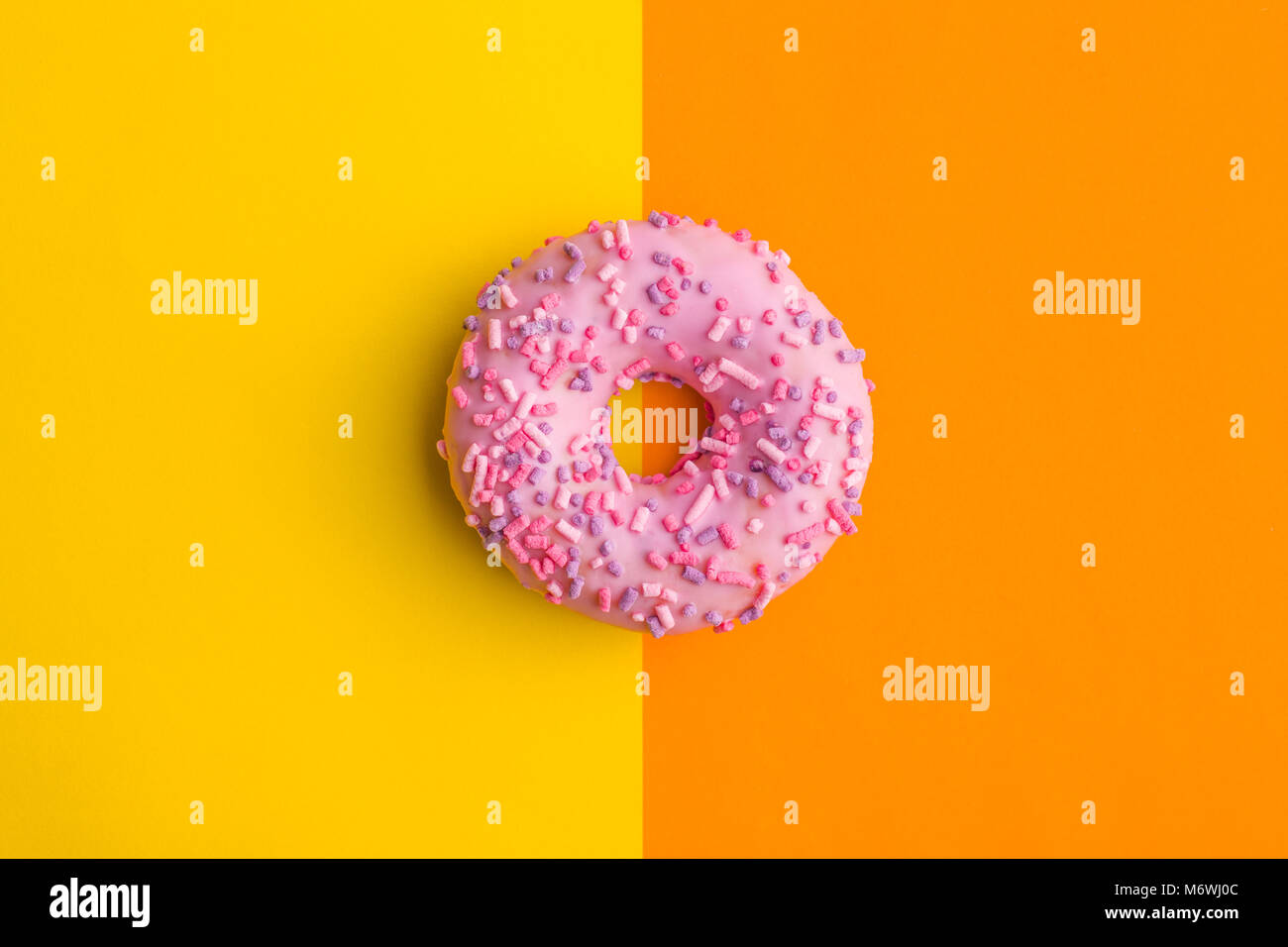 One pink donut on double colorful background. - Stock Image
