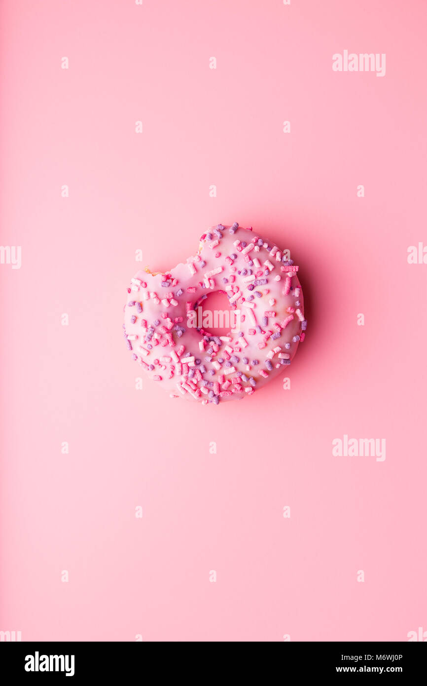 A bitten donut on pink background. - Stock Image