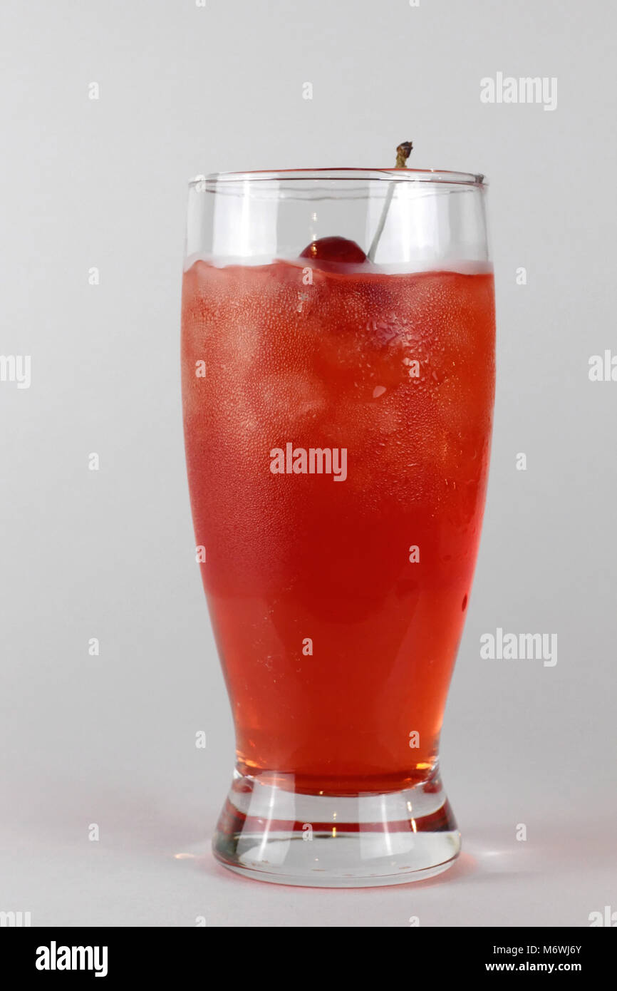 A tall glass of red Shirley Temple drink with cherry on top stands against a neutral background. - Stock Image
