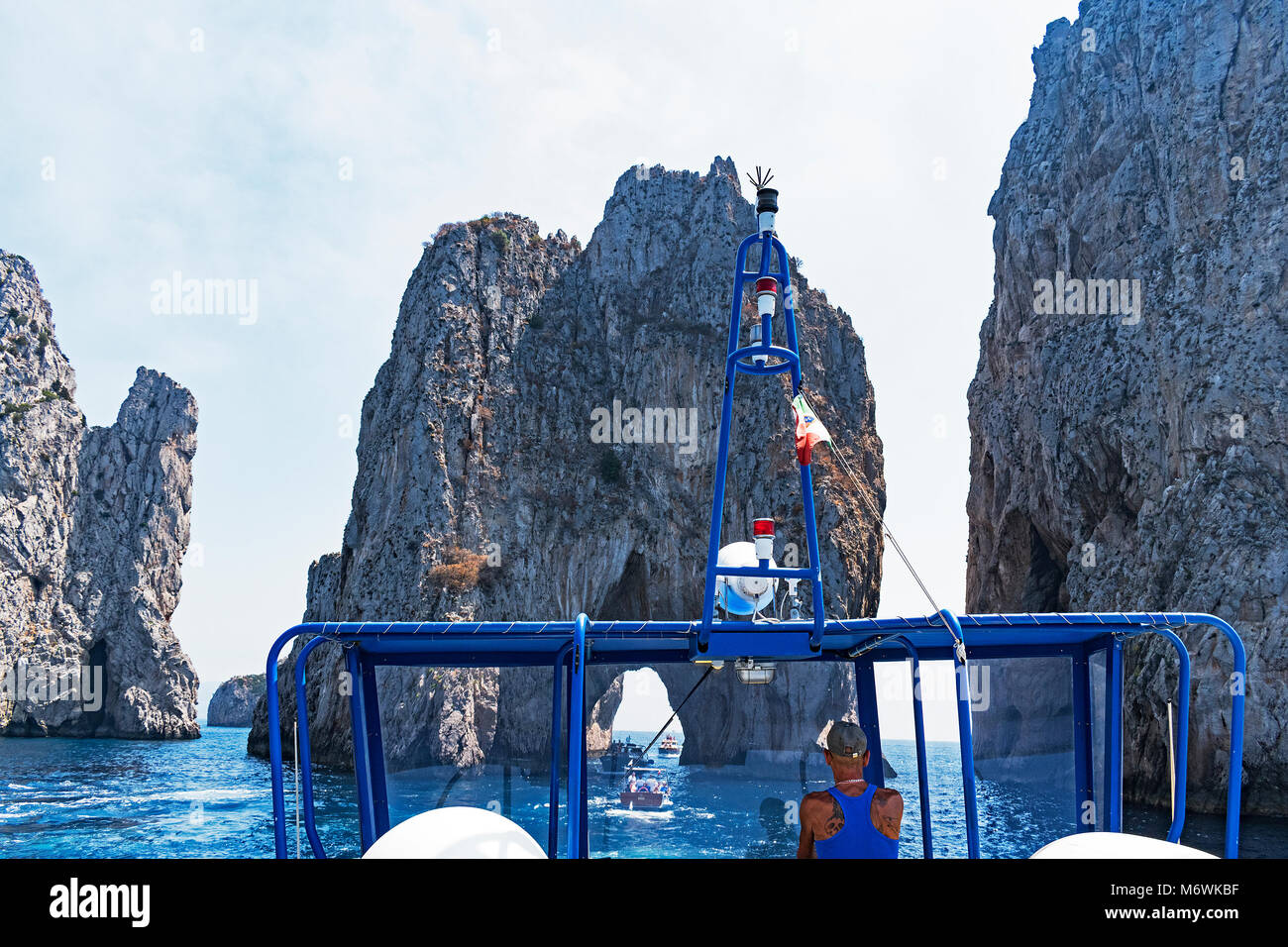 tourist boat trip approaching the famous faraglioni rocks off the island of capri in the bay of naples italy. - Stock Image