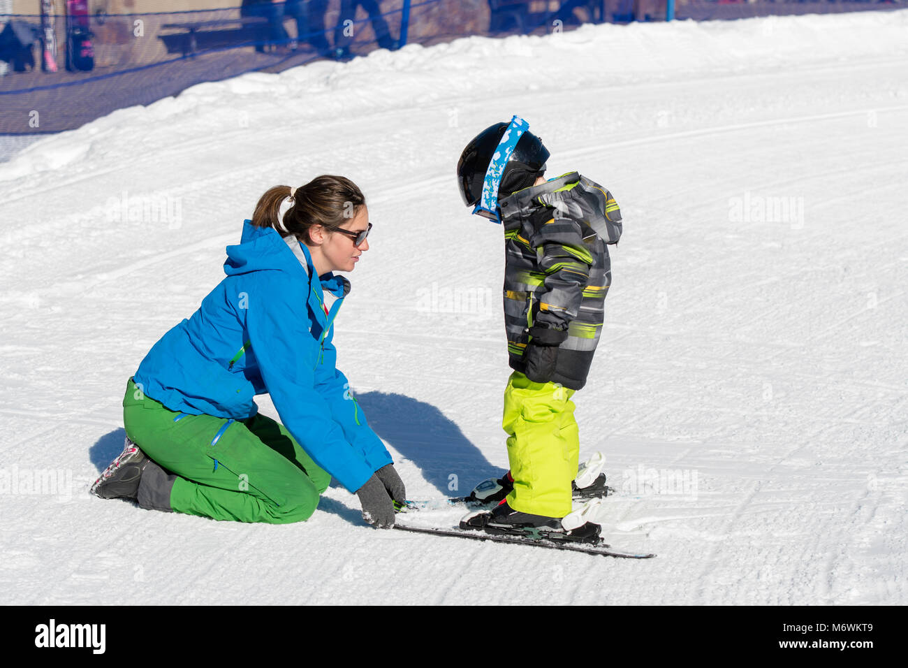Ski Instructor with 3-Year Old Toddler Boy at a Mountain Resort - Stock Image