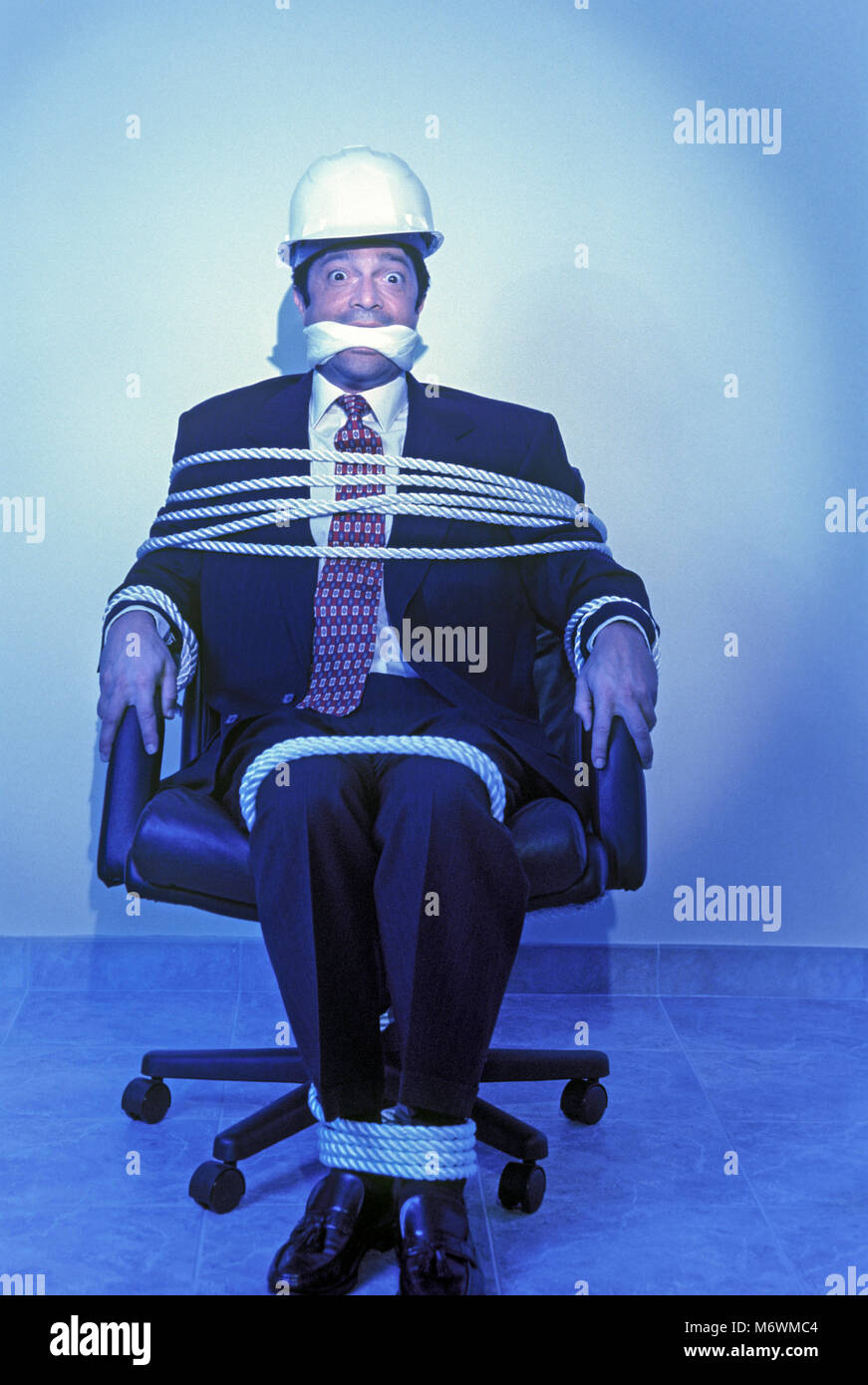 1998 HISTORICAL PORTRAIT CAUCASIAN MALE MIDDLE AGED BUSINESS MAN TIED UP TO CHAIR - Stock Image