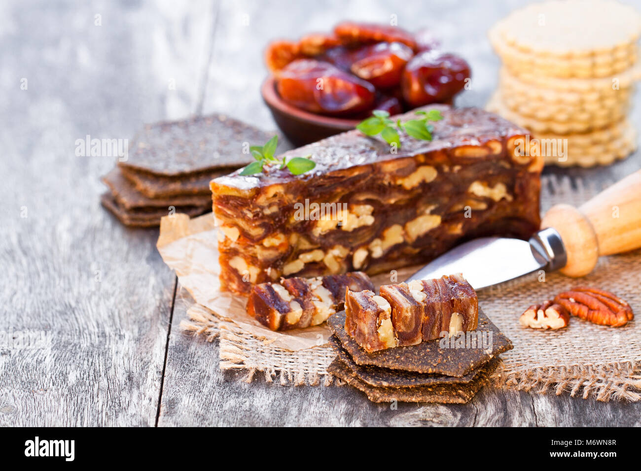 Date  walnut wedge with multigrain crackers on wooden table - Stock Image